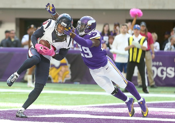 Houston Texans wide receiver DeAndre Hopkins caught the ball in the end zone for a touchdown despite pressure by Minnesota Vikings cornerback Xavier R