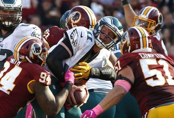 Eagles quarterback Carson Wentz, center, was sacked in the second half against the Redskins on Sunday. Washington won 27-20.