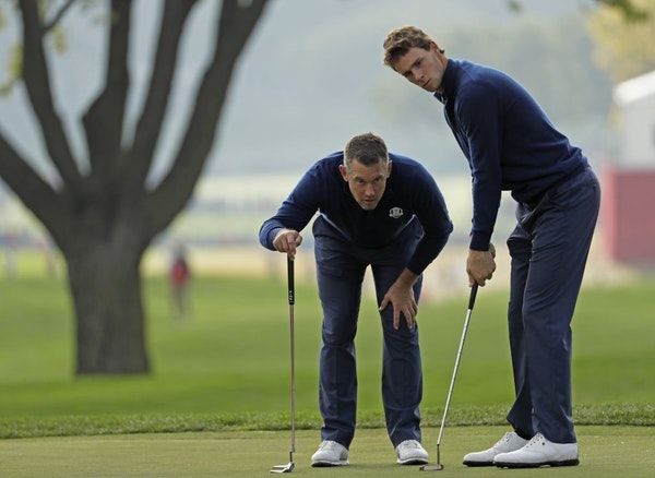 Europe�s Lee Westwood lines up a putt with Europe�s Thomas Pieters on the ninth hole during a foresomes match at the Ryder Cup golf tournament Fri
