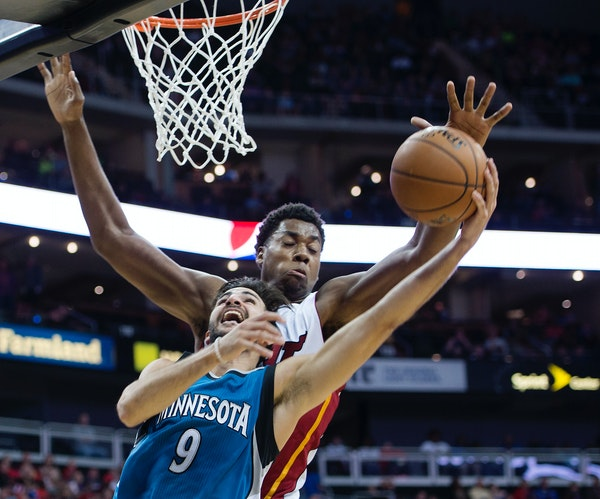 Minnesota Timberwolves guard Ricky Rubio, front, has his shot blocked by Miami Heat center Hassan Whiteside during the first half of a preseason NBA b