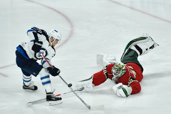 Minnesota Wild goalie Devan Dubnyk (40) knocked the puck off of the stick of Winnipeg Jets right wing Nikolaj Ehlers (27) in the first period.