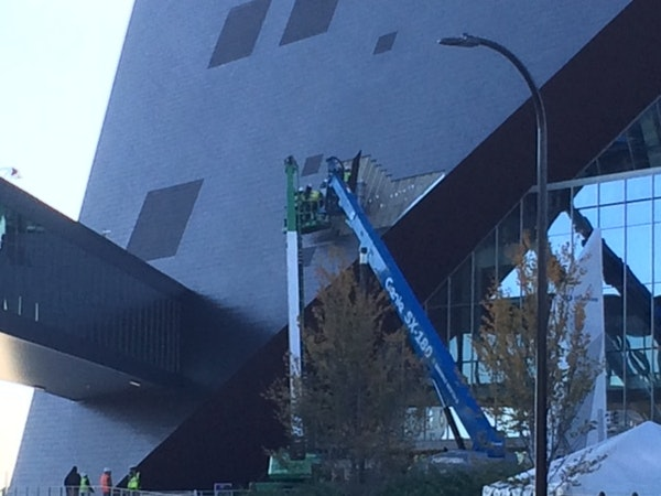 Workers examined the exterior of U.S. Bank Stadium with some of the zinc panels removed Thursday morning on the north side of the stadium.