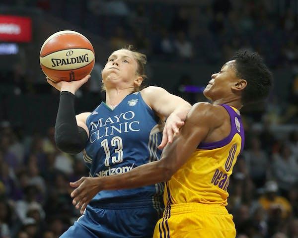 Minnesota Lynx guard Lindsay Whalen (13) got a first quarter shot off despite the defense of Los Angeles Sparks guard Alana Beard (0).