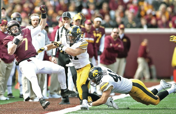 Gophers quarterback Mitch Leidner was knocked off his feet by Iowa defensive back Brandon Snyder (37) in the third quarter. Snyder also was responsibl