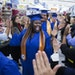 Wal-Mart Academy graduate Jessica Hall, center, walked down the aisle of Wal-Mart with fellow graduates to attend their ceremony on Tuesday.