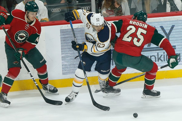 Buffalo Sabres' Tyler Ennis tries to gain control of the puck against Minnesota Wild's Joel Eriksson Ek, left, and Jonas Brodin, right, in the first p