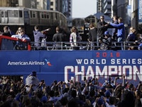 Chicago Cubs president of baseball operations Theo Epstein and general manager Jed Hoyer, right, point to each other as they acknowledge fans during a