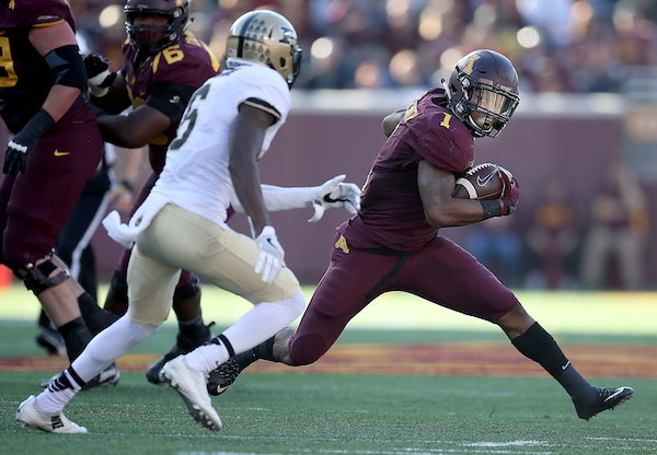 Minnesota's running back Rodney Smith ran by Purdue cornerback Myles Norwood for a first down during the second quarter Saturday.