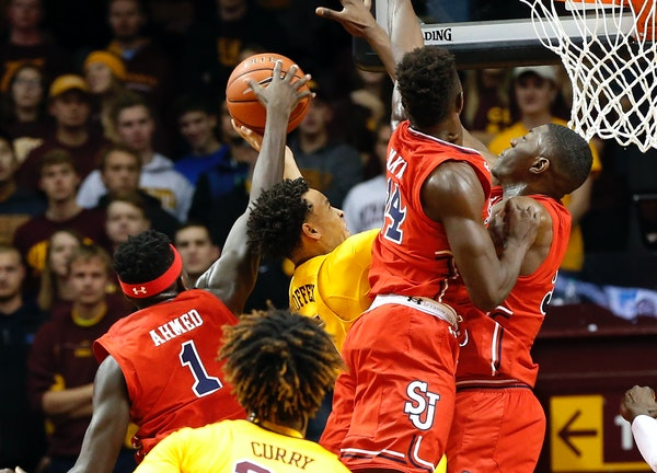 Minnesota's Amir Coffey, center in yellow, is triple-teamed by St. John's defenders on a shot attempt during the first half of an NCAA college basketb
