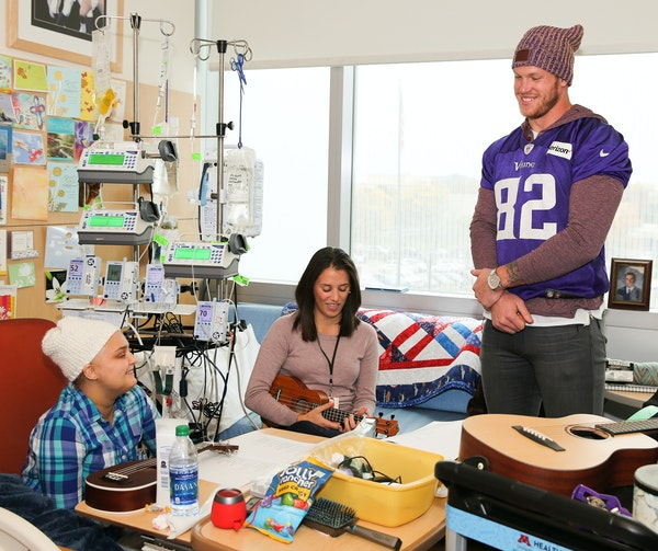 """Vikings tight end Kyle Rudolph, shown above with a family at the U's Children's Hospital, said his visits are about bringing """"a little bit of jo"""