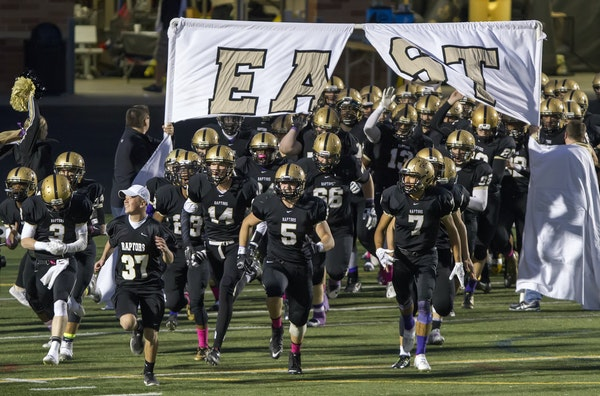 The East Ridge High School Raptors football team takes the field before playing rival Woodbury in 2015.
