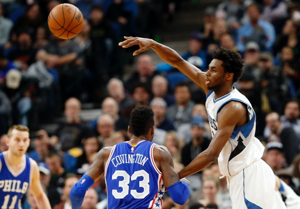 Minnesota Timberwolves' Andrew Wiggins, right, sends a pass over Philadelphia 76ers' Robert Covington in the second half of an NBA basketball game Thu