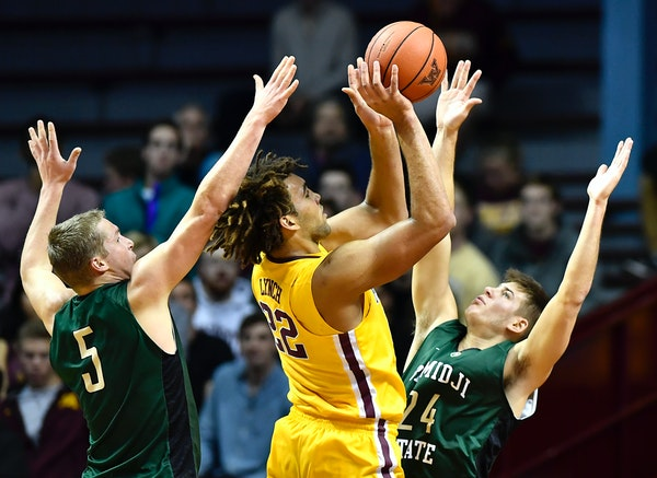 Minnesota Gophers center Reggie Lynch (22) attempted a shot in the paint while being defended by Bemidji State forward Ben Best (5) and forward Logan