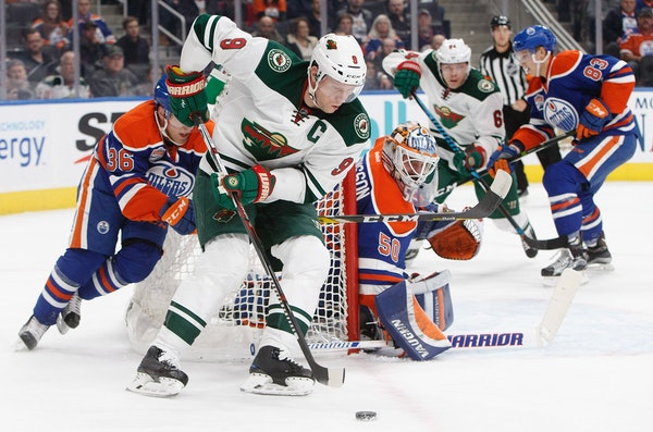 Minnesota Wild's Mikko Koivu (9) controls the puck as Edmonton Oilers' goalie Jonas Gustavsson (50) looks for the shot during the first period of an N