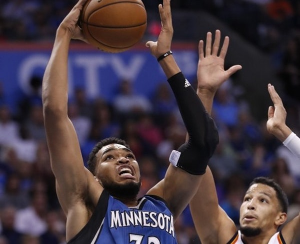Timberwolves center Karl-Anthony Towns (32) goes to the basket ahead of Oklahoma City Thunder guard Andre Roberson
