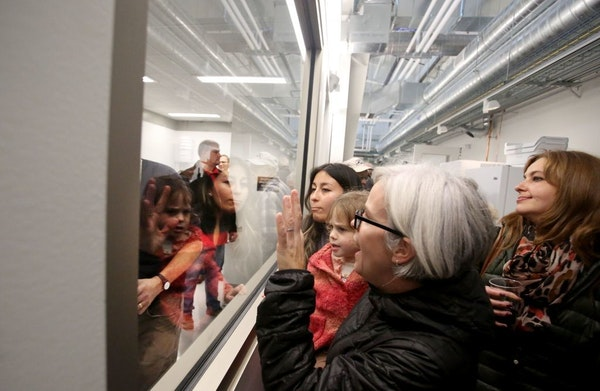 Julie Grossman of St. Paul held her daughter Juniper Kirsch, 3, as they looked through a window into the extraction room for the opening of the new 10