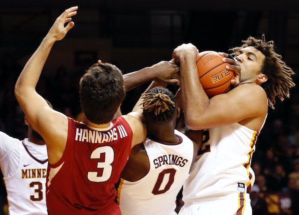 Gophers center Reggie Lynch, right, played little after he injured his ankle on a fall in the first half. His status for Friday's game against South