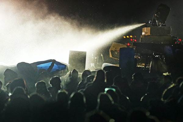 Law enforcement officers use a water cannon against protesters at a bridge leading to the DAPL Pipeline construction near the Standing Rock Reservatio