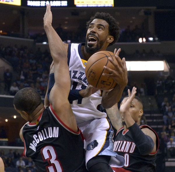 Grizzlies guard Mike Conley looked to get up a shot between Portland's C.J. McCollum and Damian Lillard on Nov. 6. Conley is making $26.5 million th