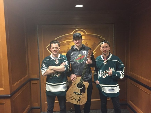 O.A.R. lead singer Marc Roberge and guitarist Richard On, after autographing and drawing a design on Zac Dalpe's guitar, pose with the Wild center aft
