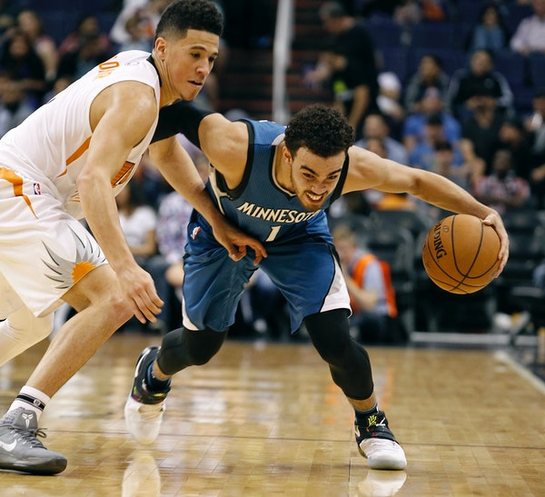 Minnesota Timberwolves guard Tyus Jones (1) advances the ball up court around Phoenix Suns' Devin Booker during the second half of an NBA basketball g