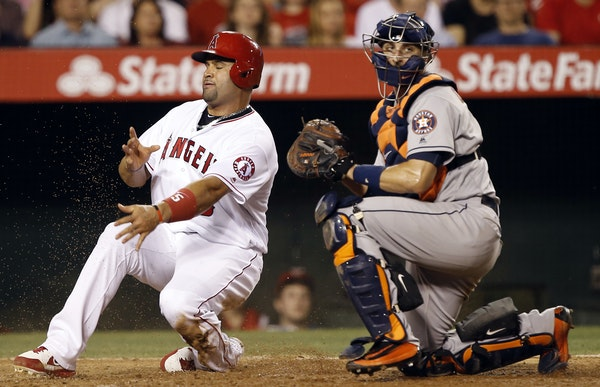 New Twins catcher Jason Castro, here tagging out Albert Pujols, is a strong defensive player whose strength is framing pitches.