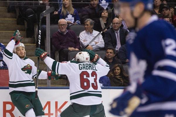 Wild right wing Chris Stewart, left, celebrates his goal with teammate Kurtis Gabriel as Maple Leafs defenseman Matt Hunwick skates by during the firs