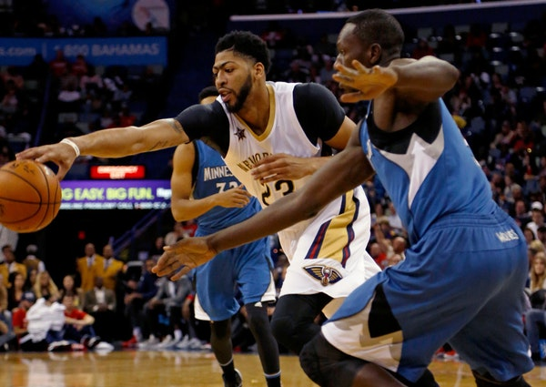 Pelicans forward Anthony Davis, left, reaches for a loose ball against Minnesota's Gorgui Dieng, right, during the first half Wednesday in New Orleans