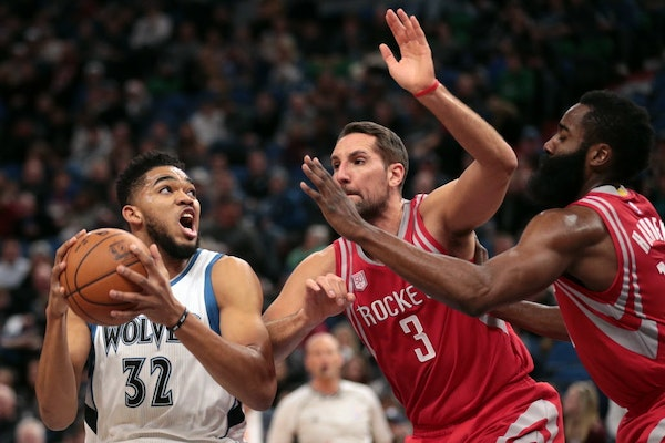 Minnesota Timberwolves center Karl-Anthony Towns (32) drives to the basket as Houston Rockets forward Ryan Anderson (3) and Houston Rockets guard Jame