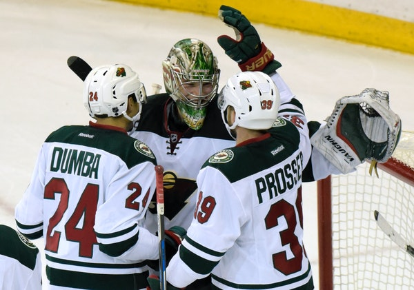 Minnesota Wild goaltender Darcy Kuemper celebrates with Matt Dumba (24) and Nate Prosser (39) after the Wild defeated the New York Rangers 7-4 in an N