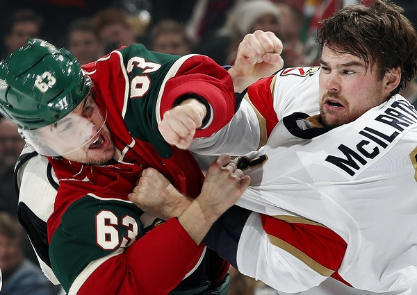 Kurtis Gabriel (63) and Dylan Mcilrath (8) fought in the first period during Tuesday night's game. ] CARLOS GONZALEZ cgonzalez@startribune.com - Decem