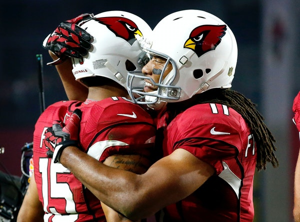 Arizona Cardinals wide receiver Michael Floyd (15) celebrates his touchdown catch with teammate Larry Fitzgerald (11) during the first half of an NFL
