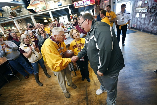 Gophers football coach Tracy Claeys made a surprise appearance as he presented Warren and Ardella Quarnstrom with a football during a breakfast Tuesda