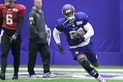 Adrian Peterson, wearing a knee brace, carried the ball while under the watchful eye of head trainer Eric Sugarman.