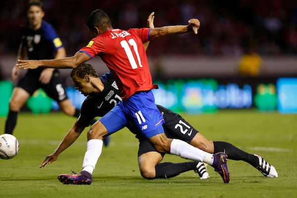Costa Rica's Johan Venegas (11) and United States' Timothy Chandler fight for the ball during a 2018 World Cup qualifying soccer match in San Jose, Co