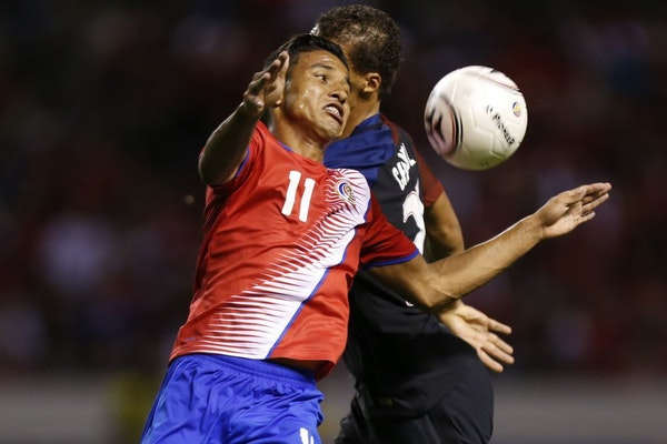 Costa Rica's Johan Venegas (11) fights for the ball against United States' Timothy Chandler during a 2018 World Cup qualifying soccer match in San Jos