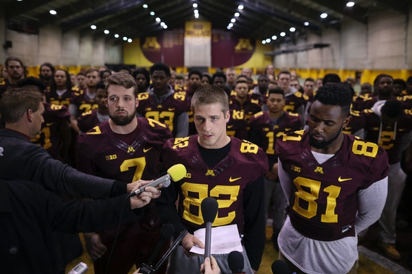 Wide receiver Drew Wolitarsky, center, flanked by quarterback Mitch Leidner, left, and tight end Duke Anyanwu, and with the rest of the team standing