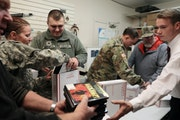 From the left, Brad Rixmann, Spc. Deanna Rice and Sgt. Banshee Barnett, Spc. Richard Polson and others packed boxes of gifts for soldiers overseas.