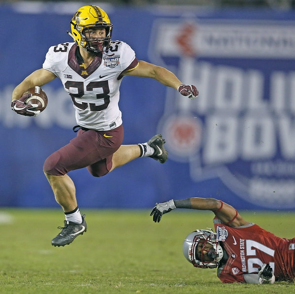 Gophers running back Shannon Brooks ran over Washington State cornerback Marcellus Pippins during the fourth quarter of the Holiday Bowl on Tuesday. B