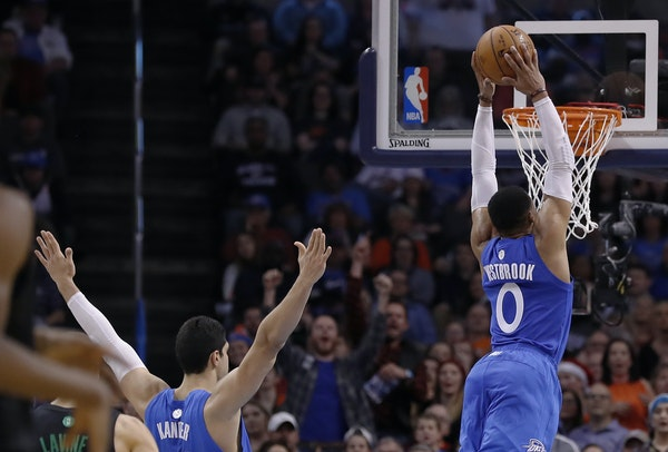 Thunder guard Russell Westbrook went up for a dunk against the Wolves as center Enes Kanter reacted Sunday night. Both Westbrook and Kanter had big ga