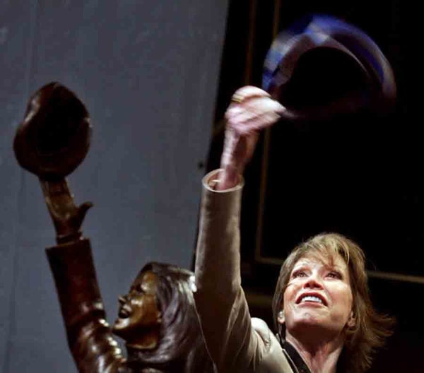 In the May 8, 2002, photo, actress Mary Tyler Moore, standing beside a statue of her in downtown Minneapolis, tossed another tam as the statue was unv