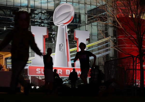 Fans play football outside of the NFL Experience ahead Super Bowl 51 Friday, Feb. 3, 2017, in Houston.