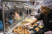 Food service assistant Arica Burgess served chicken with potatoes and rolls for lunch at a Minneapolis school in 2017.