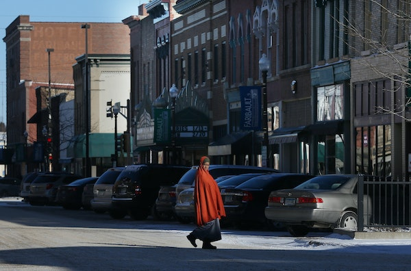 A woman walked across Central Avenue on a cold morning Wednesday in Faribault, Minn. Somali immigrants now run a restaurant, grocery and home health c