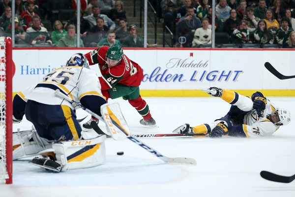 Wild center Mikael Granlund (64) crosses the puck to left wing Jason Zucker (16) who was able to score