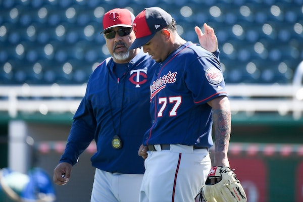 Minnesota Twins bullpen coach Eddie Guardado (18) patted pitching prospect Fernando Romero (77) on the back after Romero finished pitching during live