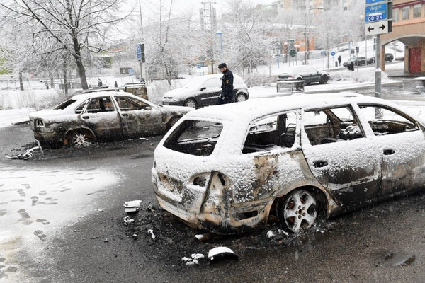In this picture taken on Monday, Feb. 20, 2017,a policeman investigates a burned out car in the suburb of Rinkeby outside Stockholm. Police in Sweden