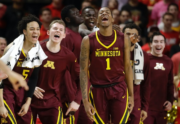 Minnesota guard Dupree McBrayer (1) reacts in front of teammates after making a 3-pointer during the second half of the team's NCAA college basketball