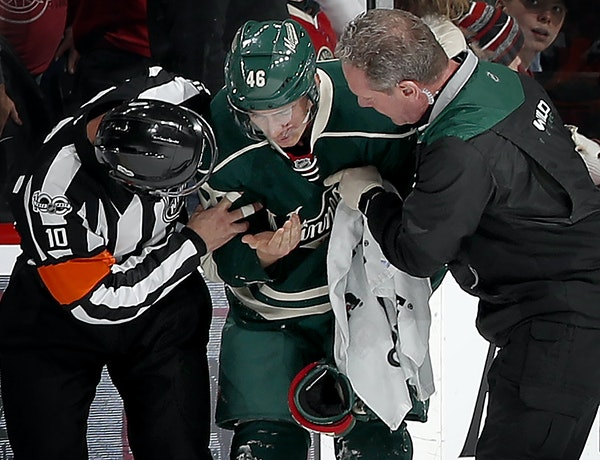 Jared Spurgeon (46) was helped off the ice after taking a stick to the face in the first period. ] CARLOS GONZALEZ ï cgonzalez@startribune.com - Febr