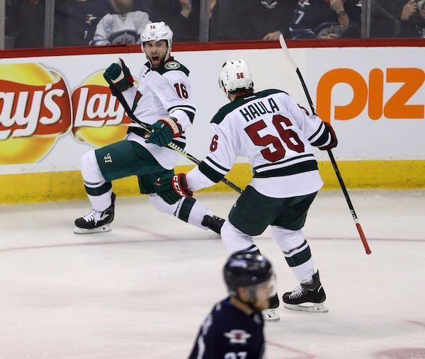 Minnesota Wild's Jason Zucker (16) celebrates with Erik Haula (56) after Zucker scored against the Winnipeg Jets during the third period of an NHL hoc